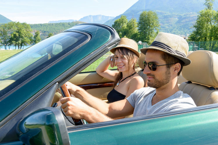 Couple traveling in convertible car