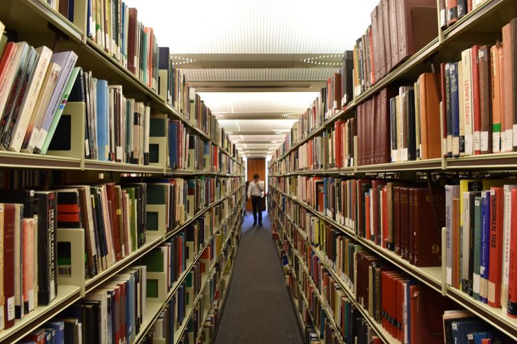 Man amidst bookshelves in library
