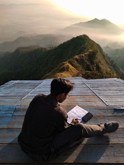 Man sitting on book by mountains against sky