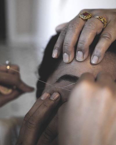 Cropped Image Of Beautician Hand Threading Eyebrows Of Woman