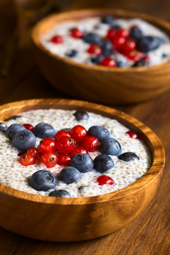 Chia (lat. Salvia hispanica) seed pudding with blueberries and redcurrants in wooden bowl, photographed on dark wood with natural light (Selective Focus, Focus one third into the pudding) Chia Dessert Meal Pudding Raw Salvia Hispanica Seed Berry Berry Fruit Blueberry Breakfast Chia Pudding Currant Dairy Dairy Product Food Food And Drink Fresh Fruit Healthy Milk Raw Food Red Currant Sweet Uncooked