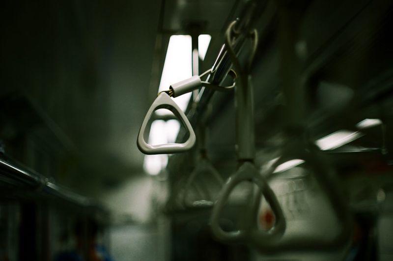 Close-Up Of Handles Hanging In Illuminated Train