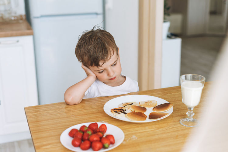 Cute toddler boy sitting with puncakes with berries in kitchen at home. child doesn't want to eat