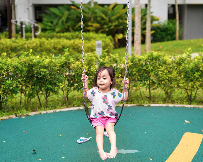 Cute small child smiling while playing swing by herself at the kid's playground,