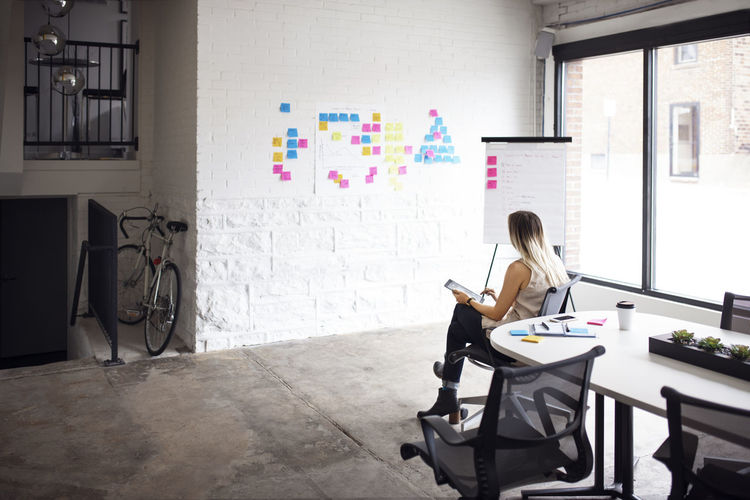 Businesswoman using tablet while sitting in creative office