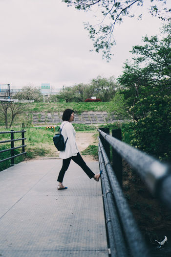 Side view of woman standing on railing against trees