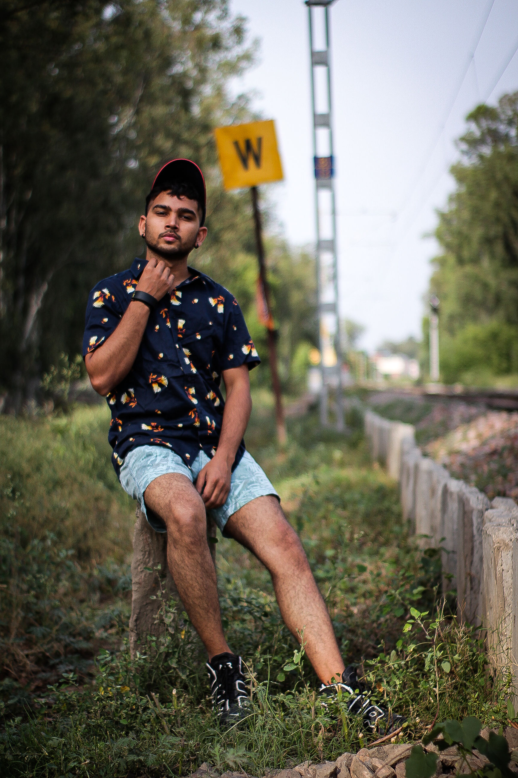 one person, full length, leisure activity, casual clothing, real people, lifestyles, plant, portrait, day, focus on foreground, tree, looking at camera, nature, front view, land, field, young adult, sitting, young men, outdoors, shorts