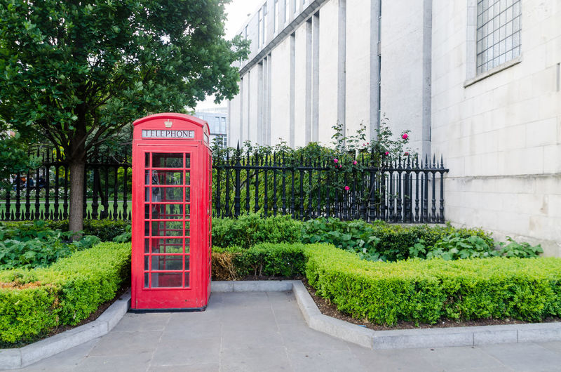 Architecture Building Exterior Built Structure Communication Day Growth London Nature No People Outdoors Pay Phone Plant Red Royal Telephone Telephone Booth Telephone Box Text Tree