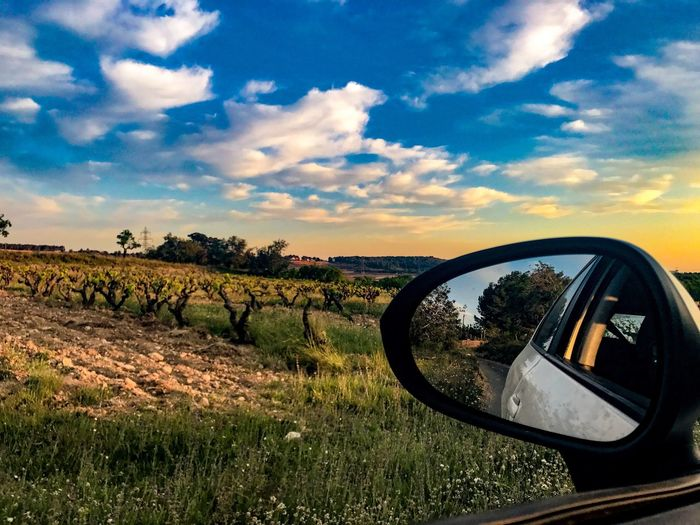 View of side-view mirror against sky