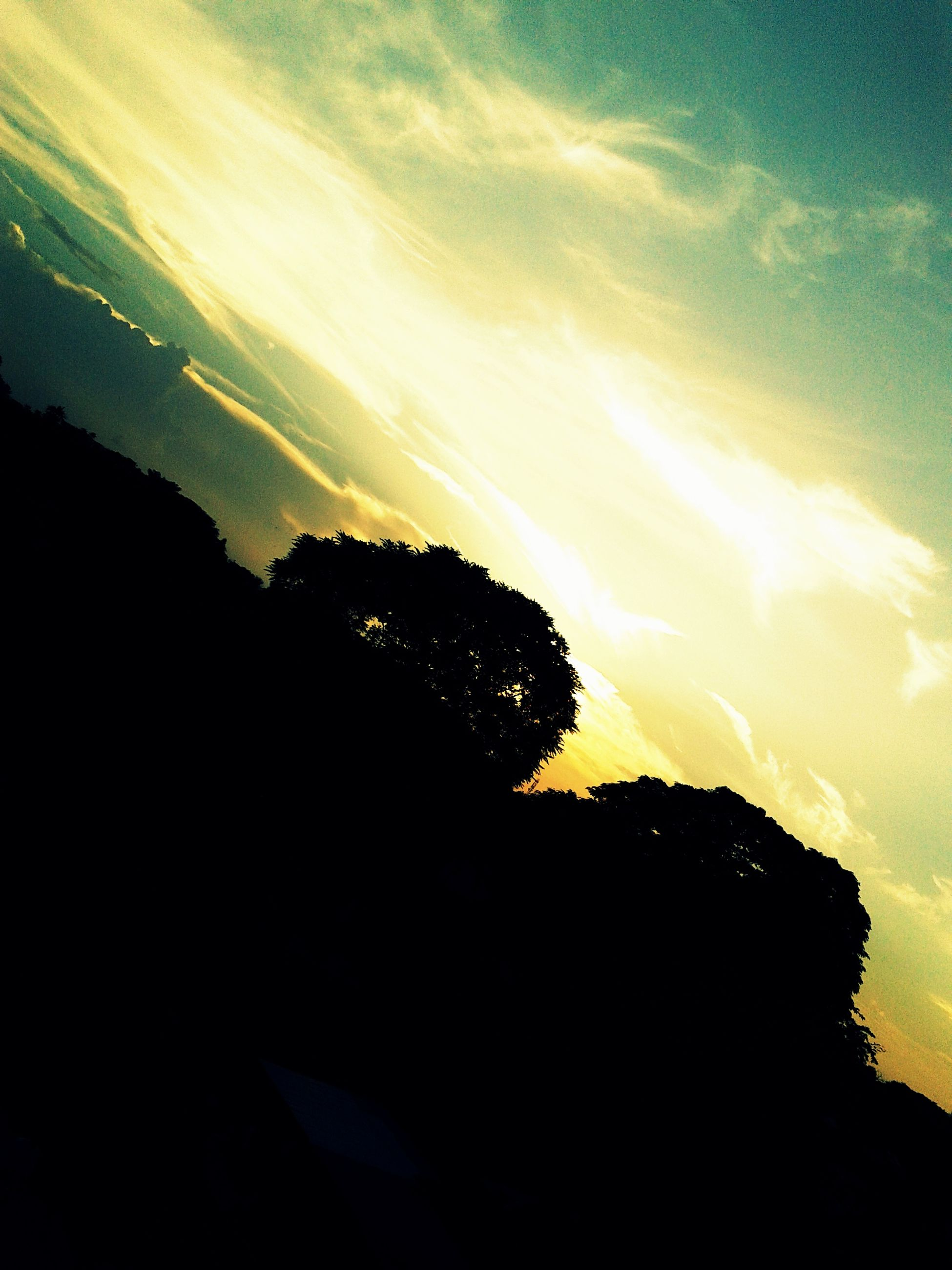 silhouette, sky, scenics, sunset, beauty in nature, tranquil scene, tranquility, tree, nature, cloud - sky, sunlight, idyllic, sun, low angle view, sunbeam, outdoors, cloud, mountain, no people, dusk