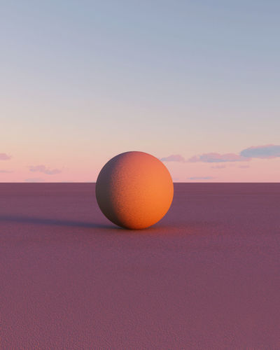 Orange ball on field against sky during sunset