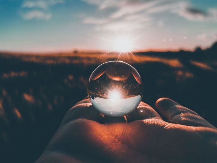 Cropped hand of person holding crystal ball against sky during sunset