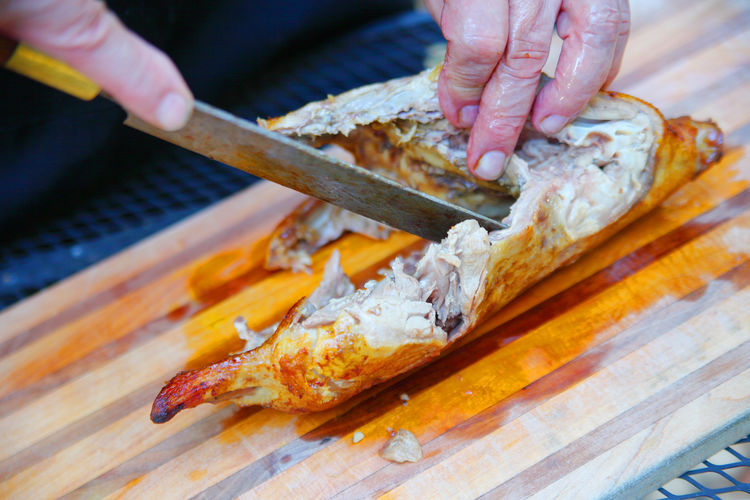 Preparing a roast duck from overhead Wood - Material Meat Close-up Holding Freshness One Person Food Preparing Food Man Hands Fingers Roast Duck Outdoors Cutting Board Messy Wood Surface Home Cooking Poultry Kitchen Knife Savory Food Main Dish Entree Kitchen Skills