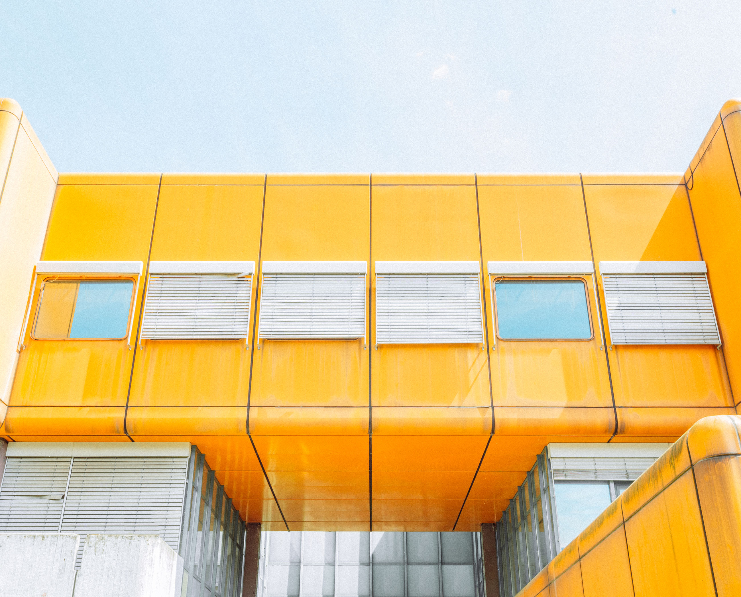 architecture, yellow, facade, built structure, building exterior, no people, low angle view, sky, building, day, outdoors, wall - building feature, nature, window, orange color, pattern, glass, city, industry