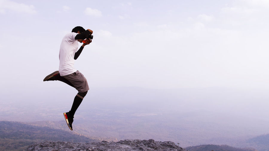Man photographing while jumping against sky
