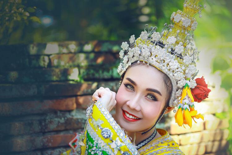 Close-up portrait of beautiful woman wearing headdress against brick wall