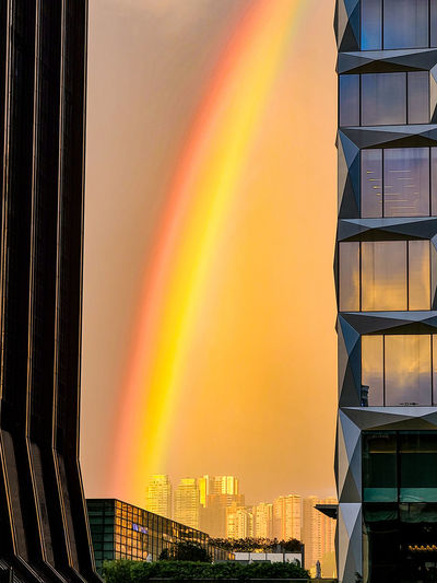 Low angle view of rainbow over buildings against sky during sunset