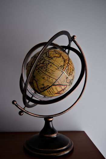 Close-up of globe on table against white wall