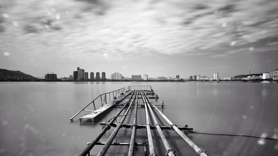Abandoned Pier Over River Against Sky