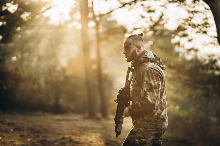 Side view of army soldier holding gun standing in forest
