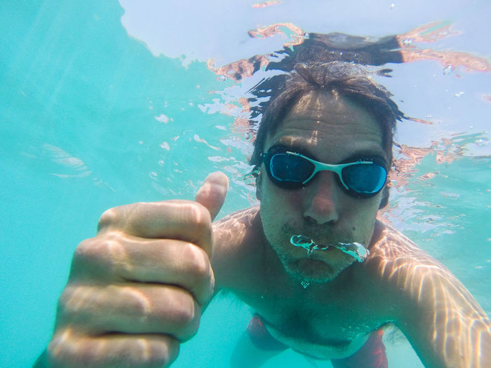 Portrait of shirtless man gesturing thumbs up in turquoise sea