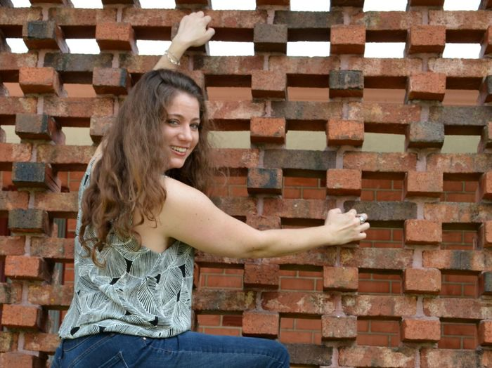 Portrait of smiling woman standing against brick wall