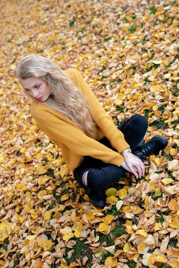 High angle view of young woman sitting on yellow leaves during autumn