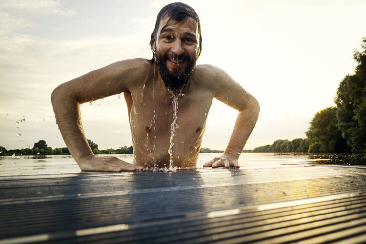 Portrait of shirtless man in lake against sky