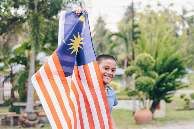 Portrait Of Smiling Boy Holding Malaysian Flag