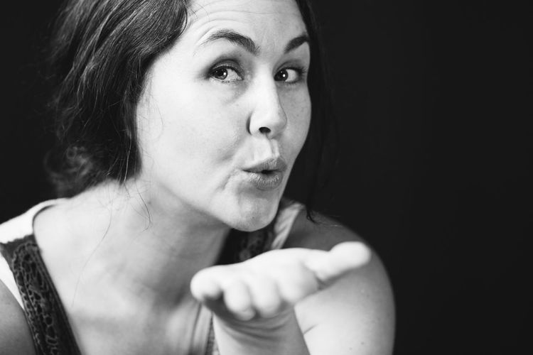 Close-up portrait of woman blowing kiss against black background