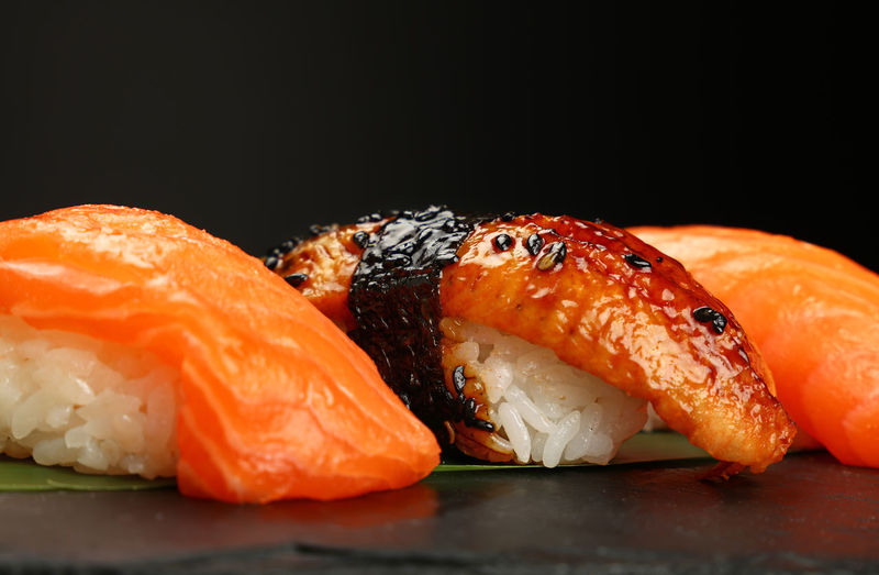 Close up sushi with salmon and eel over black background, low angle view Food And Drink Food Seafood Freshness Japanese Food Sushi Healthy Eating Fish Black Background Close-up Rice Salmon - Seafood Studio Shot Ready-to-eat Asian Food No People Rice - Food Staple Sushi Eel Sushi Rolls Low Angle View