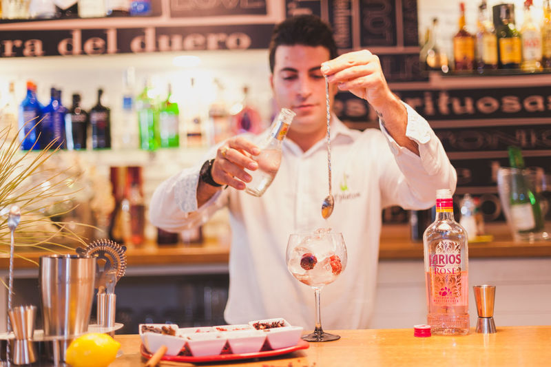 Young bartender preparing drink at counter