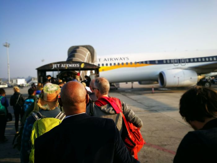 Rear view of people at airport against sky