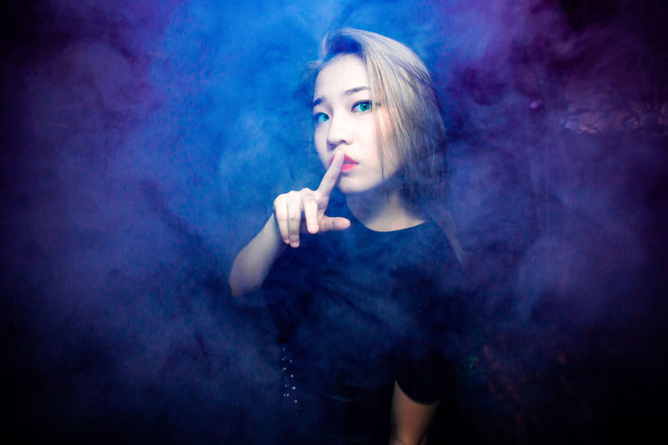 Portrait of a young woman smoking over black background