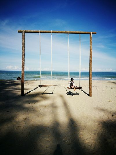 Girl on swing at beach against sky