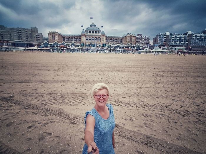 Portrait of smiling senior woman holding monopod while standing at beach against government building