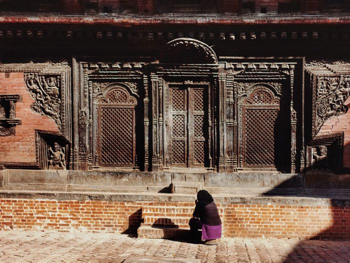 Rear view of woman walking in temple outside building
