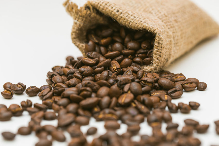 Coffee beans in a bag on a white background Abundance Black Peppercorn Brown Close-up Coffee Bean Food Food And Drink Freshness Indoors  Large Group Of Objects No People Raw Coffee Bean Roasted Coffee Bean Sack Selective Focus Still Life Studio Shot Table White Background