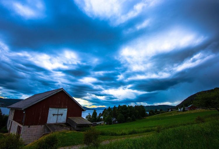 Scenic view of rural landscape against cloudy sky