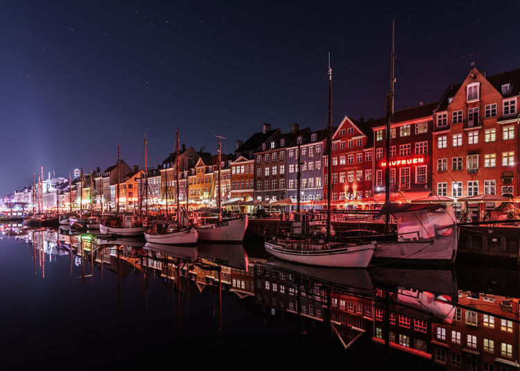 Boats moored in harbor against buildings at night