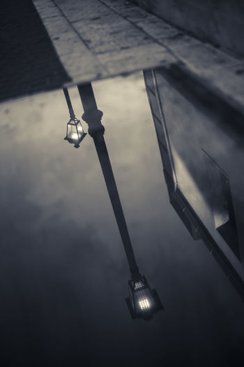 High angle view of illuminated lamp hanging against wall