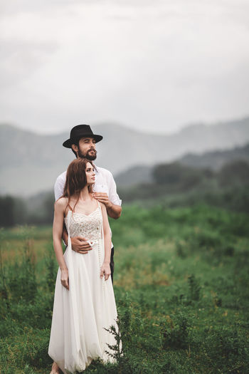 Young couple looking away while standing on grassy field against sky