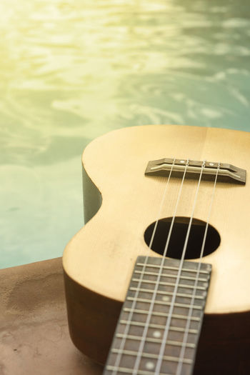 Detail of ukulele with swimming pool at the background. Holidays Music Acoustic Guitar Arts Culture And Entertainment Classical Guitar Fretboard Guitar High Angle View Music Musical Instrument Musical Instrument String Summer Ukelele Ukulele Water Woodwind Instrument