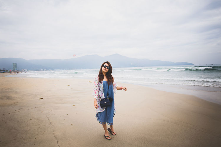 Portrait of woman standing at my khe beach against sky