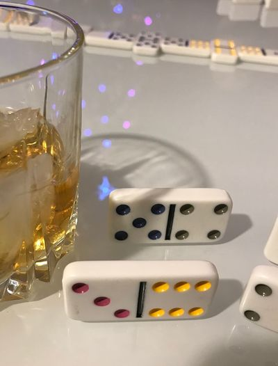 Close-Up Of Dominoes By Drink On Table