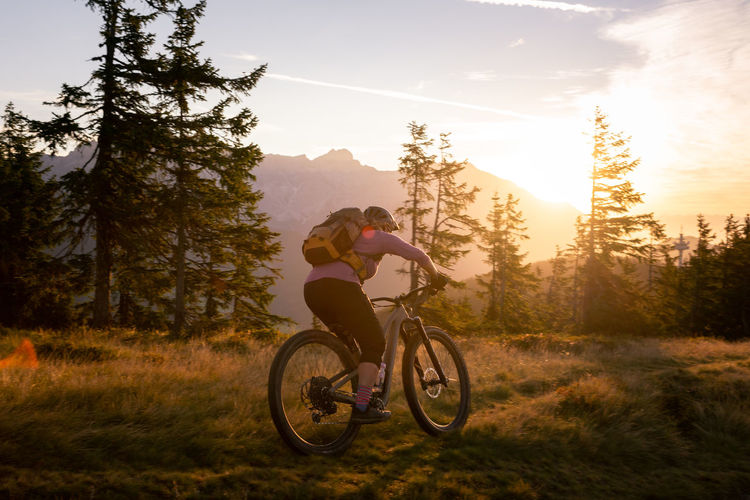 woman riding her mountain bike in early morning light on footpath, lens flare, backlight, in austria