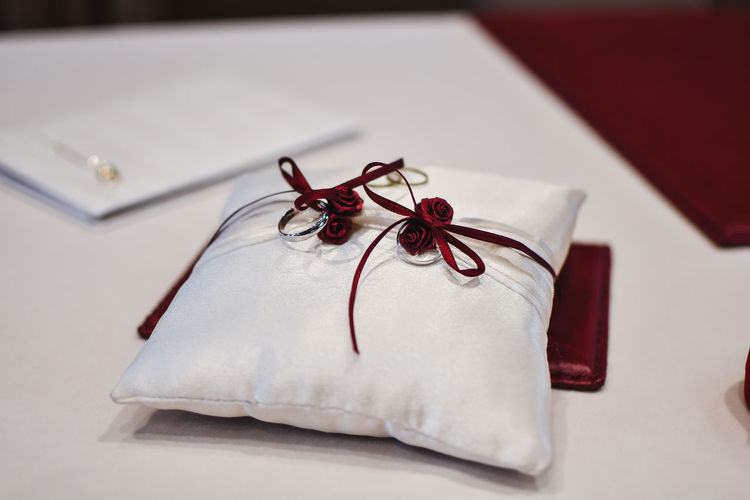 Indoors  Paper Close-up Table No People Ribbon Ribbon - Sewing Item Still Life Gift Red Tied Up Emotion White Color Tied Bow Selective Focus Bow Celebration Wrapping Paper High Angle View Surprise Gift Box Box - Container Wedding Rings