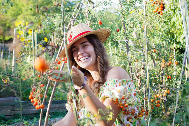 Portrait of smiling young woman against plants