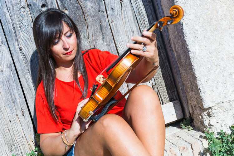 Portrait Of Young Woman Playing Violin Outdoors