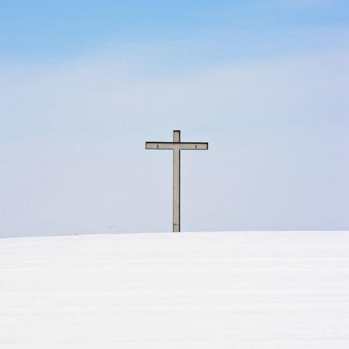 Cross on snow covered landscape against sky